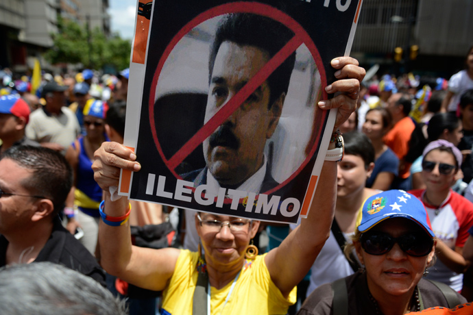 "An opponent of the Venezuelan government shows a poster with a portrait of Venezuelan President Nicolas Maduro reading ""Illegitimate"" during a May Day demonstration in Caracas on May 1, 2013 (AFP Photo / Leo Ramirez)"