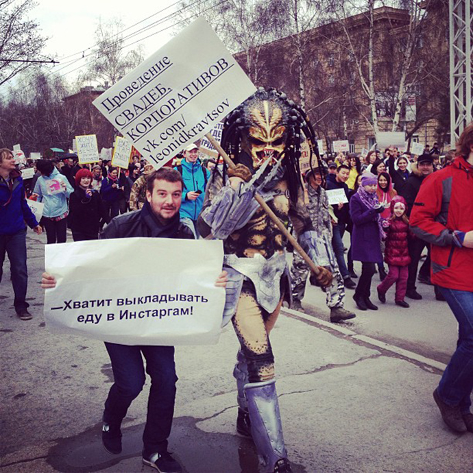 The man in a Predator costume holds a sign saying: 'Organization of weddings, corporate parties', with the other Monstration participant demanding: 'Stop posting food on Instagram!' (Image from instagram user@artemtiunov)