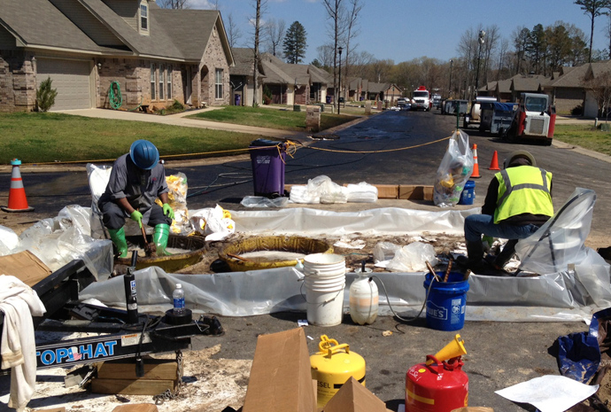 Workers scrub crude oil from their boots in the Northwoods subdivision where an ExxonMobil pipeline ruptured in Mayflower, Arkansas, April 1, 2013 (Reuters / Suzi Parker)