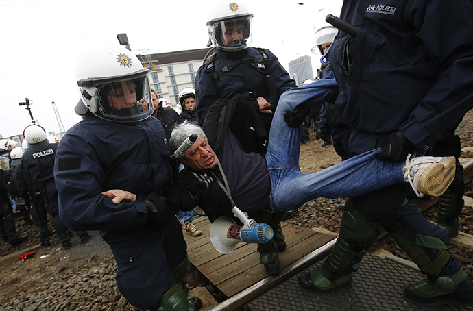 German riot police carry a left-wing protestor from the railway tracks as protestors block the tracks during a demonstration against a right-wing rally in Frankfurt, May 1, 2013. (Reuters / Kai Pfaffenbach)