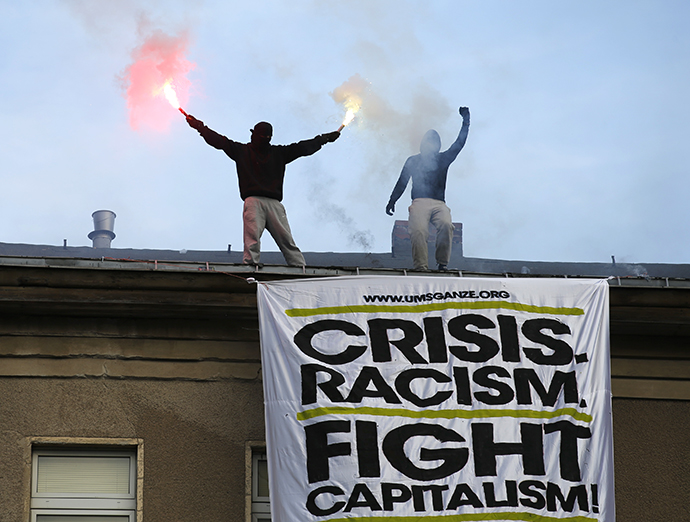 Demonstrators burn flares on the roof of a building above a huge placard during May Day protests in Berlin, May 1, 2013. (Reuters /Fabrizio Bensch)