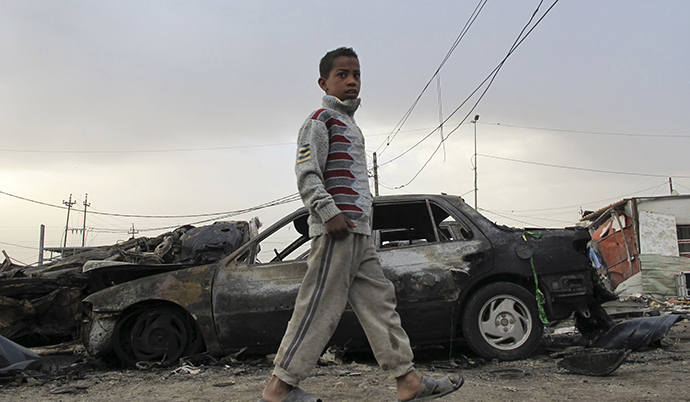 A boy walks near the site of a car bomb attack in al Habibya district in Baghdad April 16, 2013. (Reuters / Saad Shalash)