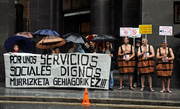 Three men in a barrel costumes hold placards against government's social cuts during a protest called by several social groups in front of the ruling Basque Nationalist Party (PNV) headquarters in the northern Spanish city of Bilbao on May 2, 2013 (AFP Photo / Rafa Rivaz)