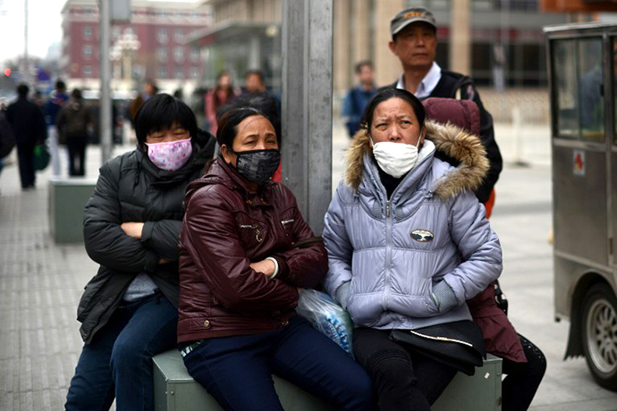 A group of Chinese women wear face masks as they sit on a street side in Beijing on April 19, 2013. (AFP Photo / Wang Zhao)