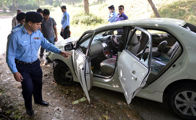 Pakistani police officials examine the bullet-riddled car of slain government prosecutor Chaudhry Zulfiqar after an attack by gunmen in Islamabad on May 3, 2013. (AFP Photo / Aamir Qureshi)