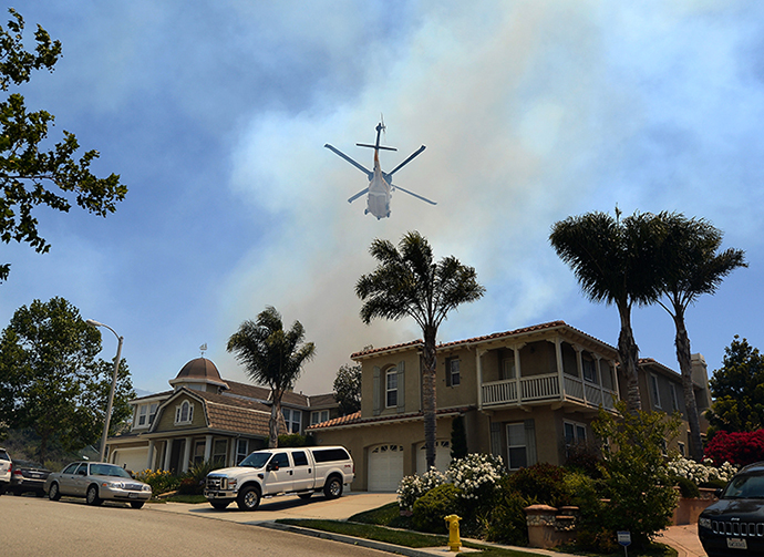 A fire fighting helicopter comes in to make a water drop behind some home threatened by a wildfire on May 2, 2013 in Newbury Park, California. (AFP Photo / Getty Images / Kevork Djansezian)