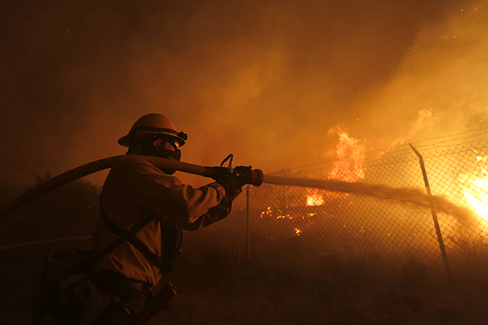A firefighter battles to protect a CalTrans Maintenance Station and Fuel Depot from the Springs Fire near Pacific Coast Highway and the Los Angeles County Line at Malibu, California, May 2, 2013. (Reuters / Patrick Fallon)