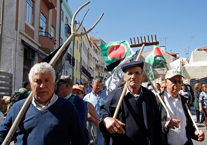 Farmers march to the Parliament in Lisbon with flags and their old tools April 17, 2013 (Reuters / Jose Manuel Ribeiro)