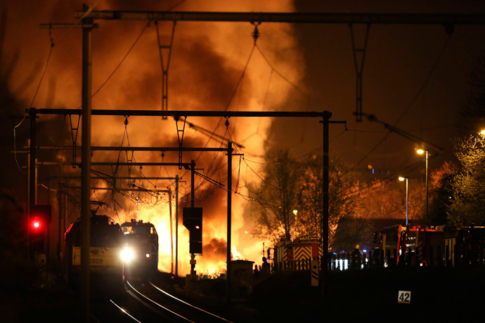 Firemen work next to a train on fire on a track near Schellebelle, 20 kms east of Gent on May 4, 2013 (AFP Photo / Belga / Nicolas Maeterlinck)