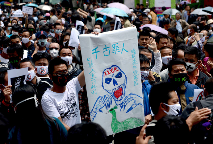 Cemonstrators display banners during a protest against plans for a factory which will produce paraxylene (PX), a toxic petrochemical used to make fabris, in Kunming, southwest China's Yunnan province on May 4, 2013 (China out / AFP Photo)