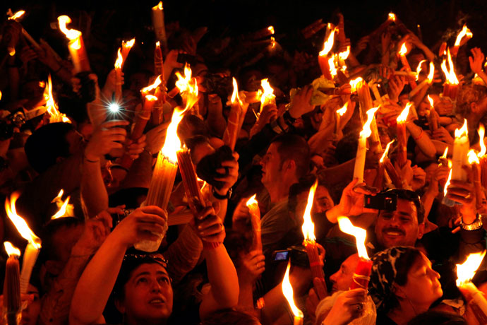 Christian Orthodox worshippers hold up candles lit from the 'Holy Fire' as thousands gather in the Church of the Holy Sepulchre in Jerusalem's old city on May 4, 2013.(AFP Photo / Gali Tibbon)