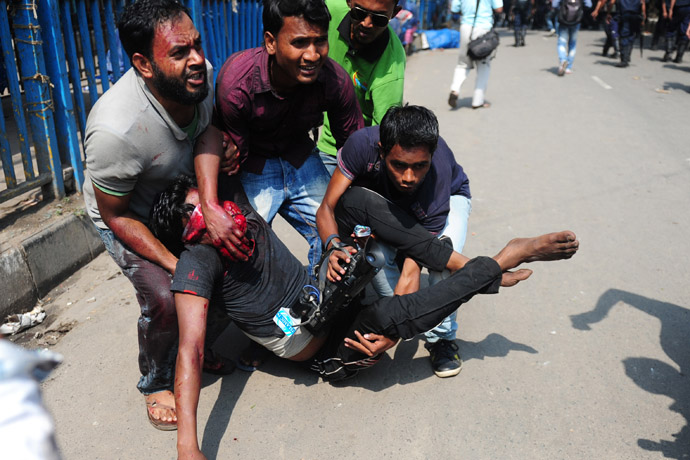 Civilian people carry an injured Islamist protestor during clashes with police in Dhaka on May 5, 2013. (AFP Photo/Munir uz Zaman)