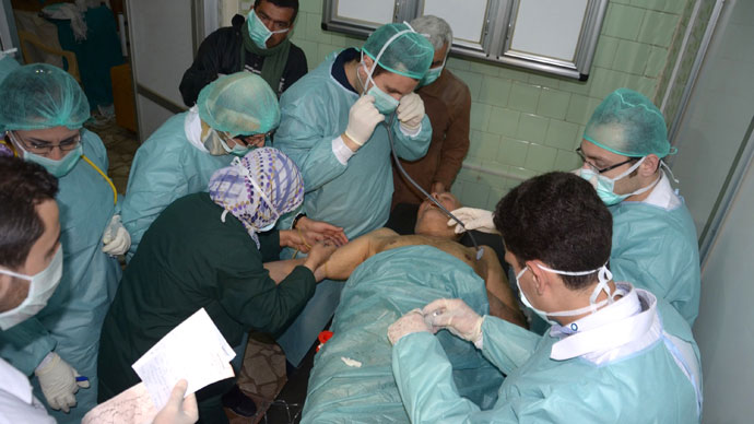 Medics and other masked people attend to a man at a hospital in Khan al-Assal in the northern Aleppo province, as Syria's government accused rebel forces of using chemical weapons for the first time. The opposition denied the claim, saying instead that government forces might have used banned weapons.(AFP Photo / HO-SANA)