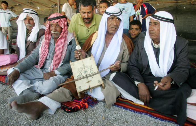 Bedouin men sit together during wedding celebrations in the village of Kusaifa in Israel's Negev desert (Reuters)