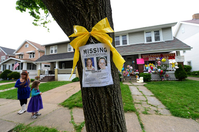 A missing person sign displaying portraits of Amanda Berry , one of the three women held captive for a decade, stands in front of her sister's house May 7, 2013 in Cleveland. (AFP Photo / Emmanuel Dunand)