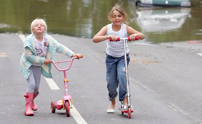 Children play on scooters in Treeton near Sheffield, England. (AFP Photo / Paul Ellis)