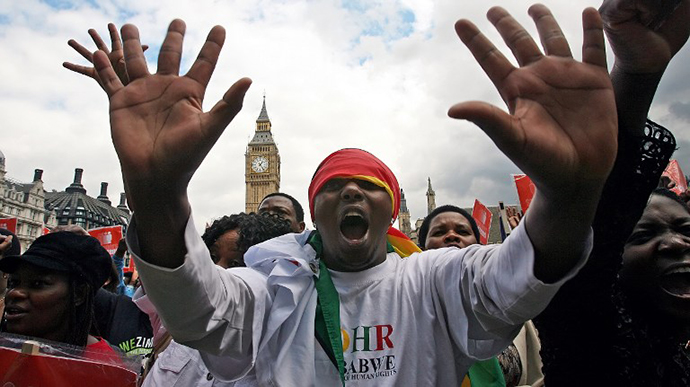 "The ""Strangers into Citizens"" group organised a rally in front of the Houses of Parliament, asking the government to allow Zimbabwean immigrants the right to work and pay taxes in the United Kingdom. (AFP Photo / Leon Neal)"