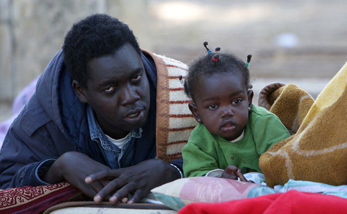 Sudanese refugees wake up at a park near the Israeli Parliament building in Jerusalem. (AFP Photo / Yoav Lemmer)
