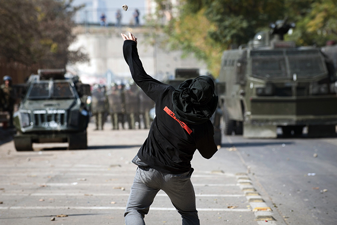 A student throews stines to riot police during a protest to demand Chilean President Sebastian Pinera's government to improve the public education quality, in Santiago, on May 8, 2013. (AFP Photo / Claudio Santana)