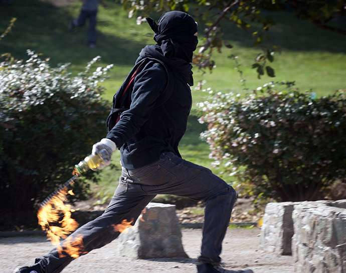 A student throws a molotov cocktail to riot policemen during a protest to demand Chilean President Sebastian Pinera's government to improve the public education quality, in Santiago, on May 8, 2013. (AFP Photo / Claudio Santana)