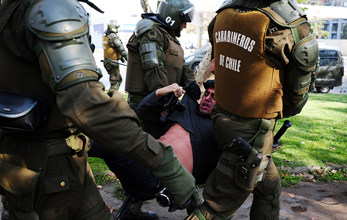 Riot policemen arrest a photographer during a student protest to demand Chilean President Sebastian Pinera's government to improve the public education quality, in Santiago, on May 08,2013. (AFP Photo / Martin Bernetti)