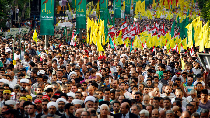 Supporters of Lebanon's Hezbollah leader Sayyed Hassan Nasrallah wave Hezbollah and Lebanese flags as they march at an anti-U.S. protest in Beirut's southern suburbs September 17, 2012.(Reuters / Sharif Karim)