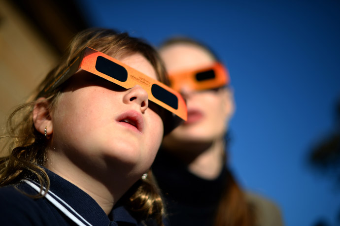 A child (L) watches a partial solar eclipse with a woman at the Sydney Observatory on May 10, 2013. (AFP Photo/Saeed Khan)