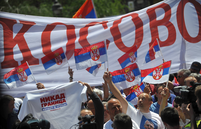 "Demonstrators hold a banner reading ""Kosovo"" and wave flags during a protest against the accord on the normalisation of relations between Serbia and Kosovo in the Serbian capital Belgrade on May 10, 2013 (AFP Photo / Andrey Isakovic)"