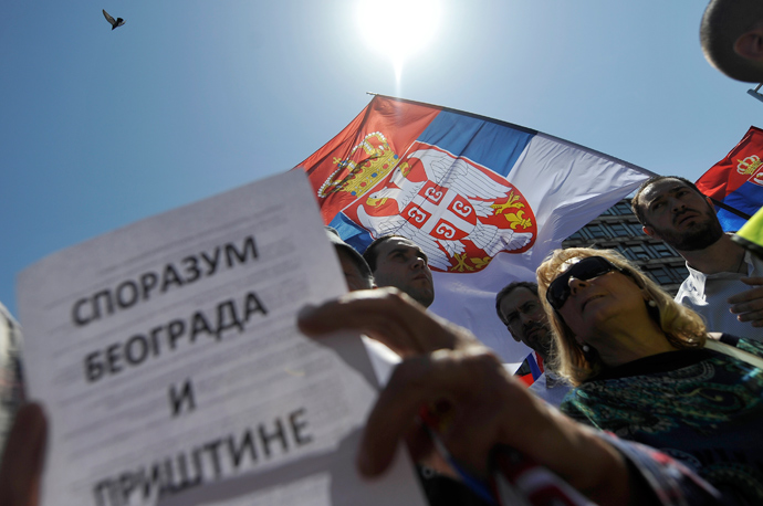 "A demonstrator reads a paper reading ""Brussels accord between Belgrade and Pristina"" during a protest against the accord on the normalisation of relations between Serbia and Kosovo in the Serbian capital Belgrade on May 10, 2013 (AFP Photo / Andrey Isakovic)"