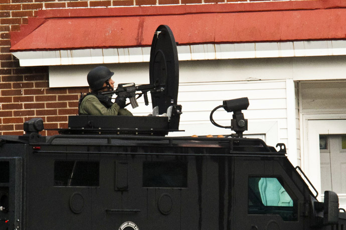 A SWAT police officer stands guard near the suspect's house (not pictured) in Trenton, New Jersey, May 11, 2013. (Reuters)
