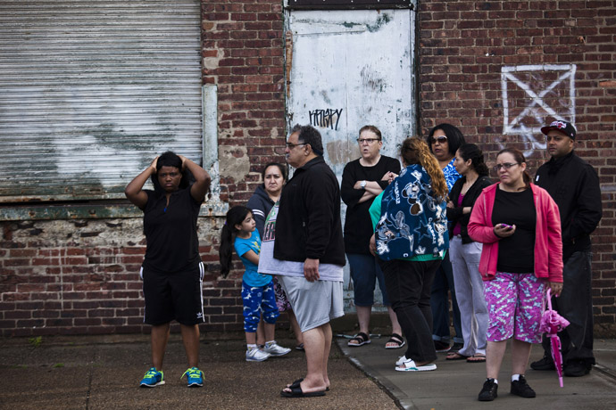 People look on at members of the police (not pictured) during a hostage situation in Trenton, New Jersey, May 11, 2013.