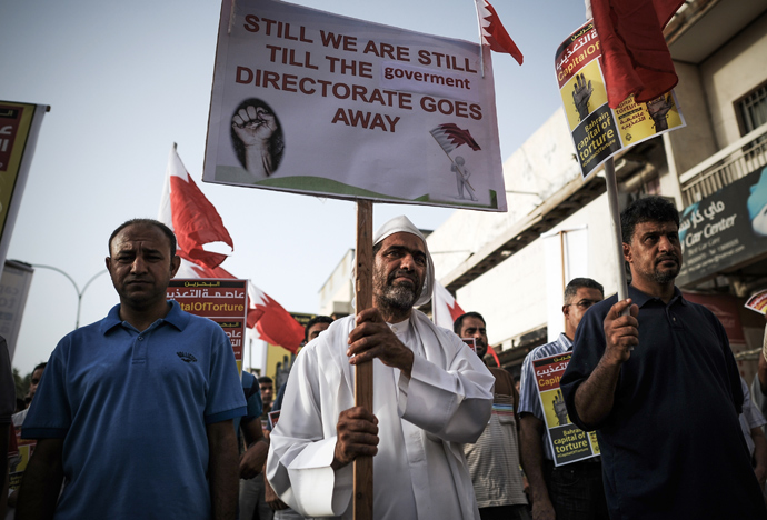 Bahraini protestors hold up placards during an anti-government protest in the village of Jidhafs, west of Manama, on May 10, 2013 (AFP Photo / Mohammed Al-Shaikh)