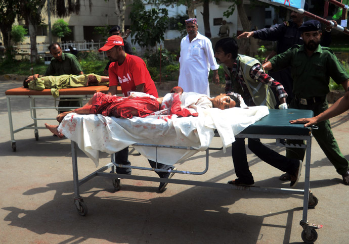 Pakistani volunteers carry injured blast victims to a hospital following a bomb explosion in Karachi on May 11, 2013. (AFP Photo/Rizwan Tabasssum)