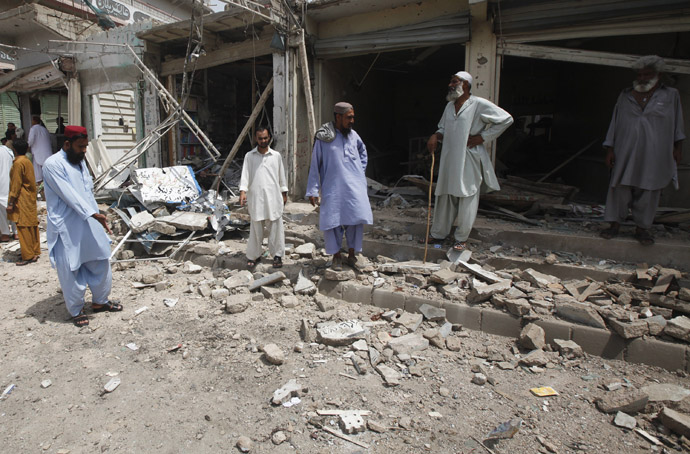 Residents gather at the site of a bomb attack near a polling station during an election, in Karachi May 11, 2013. (Reuters)