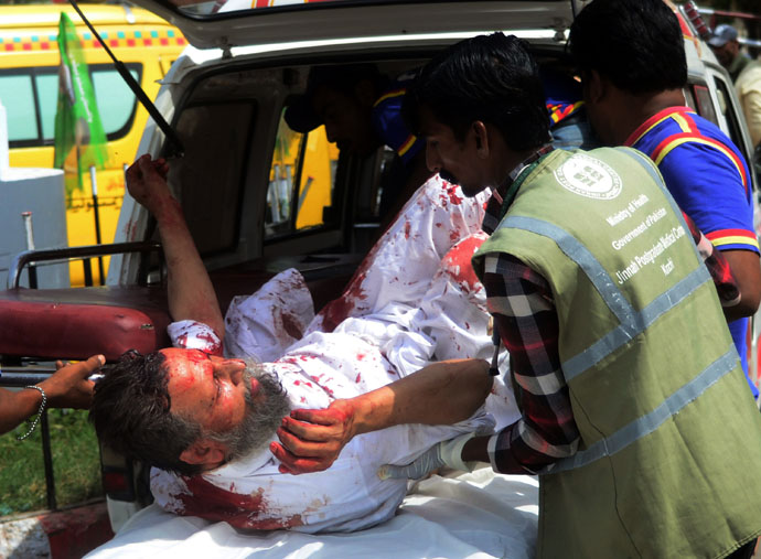 Pakistani volunteers shift an injured blast victim to a hospital following a bomb explosion in Karachi on May 11, 2013. (AFP Photo)