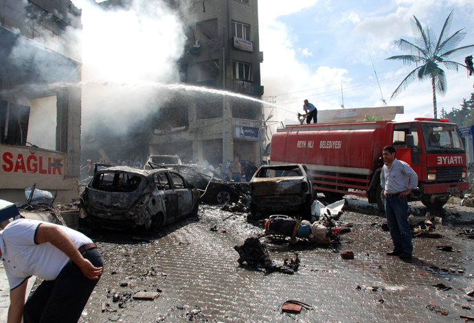 People stand on the site of a car bomb explosion on May 11, 2013 near the town hall of Reyhanli (AFP Photo / Ihlas News Agency)