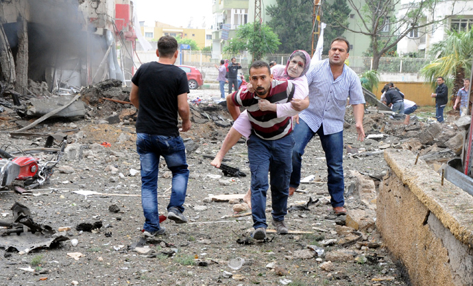 Residents evacuate a wounded woman to hospital after car bombs exploded on May 11, 2013 near the town hall in Reyhanli (AFP Photo / Ihlas News Agency)