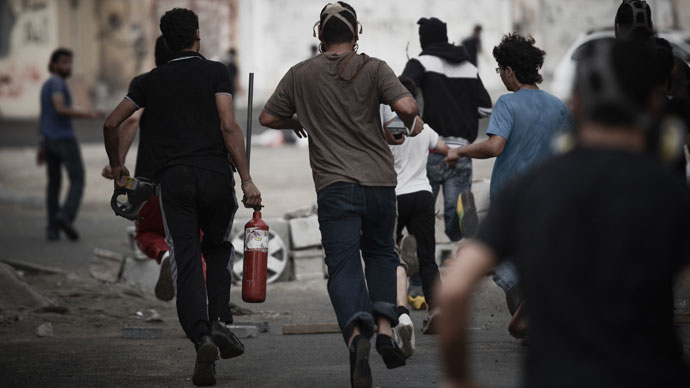 A Bahraini protester runs away carrying a pressurized fire extinguisher that is used to shot iron arrows towards riot police during clashes following a protest against the arrival of Bahrain Formula One Grand Prix on April 18, 2013.(AFP Photo / Mohammed Al-Shaikh)