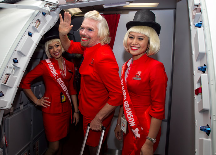 British billionaire Richard Branson (C) waves before boarding an AirAsia flight bound for Kualu Lumpur to work as a flight attendant at Perth Airport on May 12, 2013.(AFP Photo / Tony Ashby)