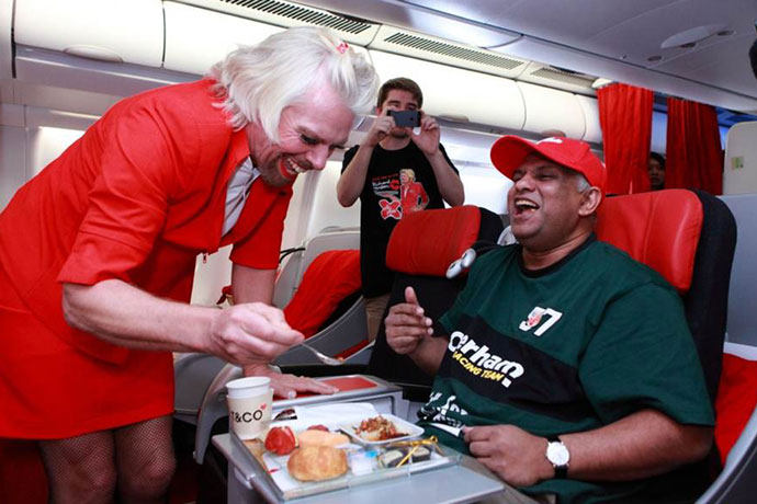 Tony Fernandes (R) being served by British billionaire Richard Branson (L), who is dressed as a female flight attendant, in the air while flying from the Australian city of Perth to the Malaysian city of Kuala Lumpur. Branson honoured a losing bet by serving as a stewardess with Fernandes over whose Formula One racing team would finish ahead of each other at the Abu Dhabi race during their debut 2010 season.(AFP Photo / Aair Asia)