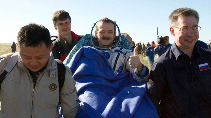 Ground personnel carry Canadian astronaut Chris Hadfield (C) after the Russian Soyuz space capsule landed some 150 km (90 miles) southeast of the town of Zhezkazgan, in central Kazakhstan May 14, 2013.(Reuters / Sergei Remezov)