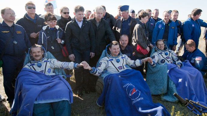 US astronaut Tom Marshburn (R), Canadian spaceman Chris Hadfield (L) and Russian cosmonaut Roman Romanenko (C) join their hands as they rest shortly after the landing aboard the Russian Soyuz space capsule some 150 km (90 miles) southeast of the town of Zhezkazgan in central Kazakhstan on May 14, 2013.(AFP Photo / Sergei Remezov)