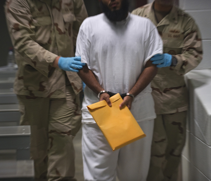 In this photo reviewed by US military officials, US military guards at Campt VI move a detainee back to his cell after he attended a lifeskills class that included resume writing at the US Detention Center in Guantanamo Bay, Cuba (AFP Photo / Paul J. Richards)