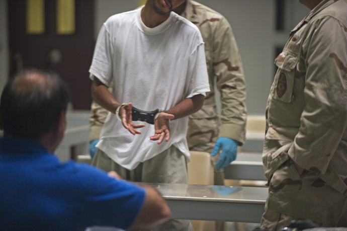 In this photo reviewed by US military officials, a detainee inside Camp VI is put in transport restraints to be taken back to his cell after after attending a life skills class that includes resume writing inside the US military detention center in Guantanamo Bay, Cuba (AFP Photo / Paul J. Richards)