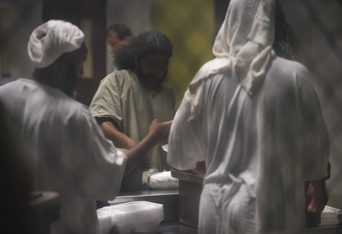 In this photo reviewed by US military officials, detainees using towels as head dress are seen inside Camp VI as they gather at a cart rolled into the communial area with thier noon meal inside the US Detention Center in Guantanamo Bay, Cuba (AFP Photo / Paul J. Richards)