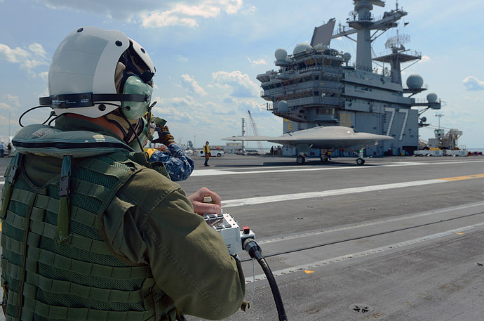This May 10, 2013 US Navy handout image shows Dave Lorenz, a Northrop Grumman deck operator, driving an X-47B Unmanned Combat Air System (UCAS) demonstrator using an arm-mounted controller on the flight deck of the aircraft carrier USS George H.W. Bush (CVN 77) while docked in Norfolk, Virginia. (AFP/Handout/US Navy/MC2 Timothy Walte)