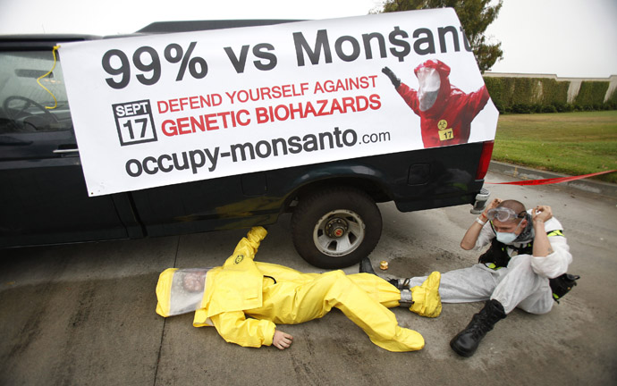 Protesters against Genetically Modified Organisms (GMO) are chained to a vehicle as they block a delivery entrance to a Monsanto seed distribution facility in Oxnard, California September 12, 2012. (Reuters/Mario Anzuoni)