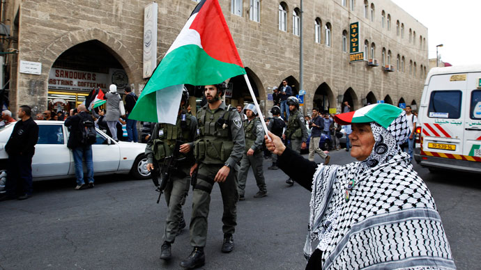 A Palestinian protestor holds a Palestinian flag during a demonstration for Nakba (Catastrophe) day, near Damascus Gate at Jerusalem's old city May 15, 2013.(Reuters / Ammar Awad)