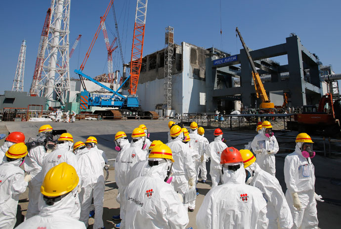 Members of the media wearing protective suits and masks are escorted by Tokyo Electric Power Co (TEPCO) employees as they visit near the No.4 reactor (C) and the construction of a foundation (R) for storage of melted fuel rods at TEPCO's tsunami-crippled Fukushima Dai-ichi nuclear power plant in the town of Okuma, Fukushima prefecture on March 6, 2013.(AFP Photo / Issei Kato)