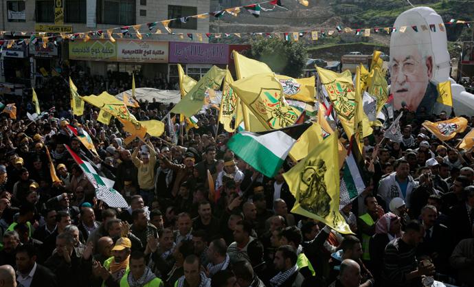 Palestinians wave Fatah movement flags and hold a large portrait of Palestinian president Mahmud Abbas (AFP Photo / Jaafar Ahtiyeh)